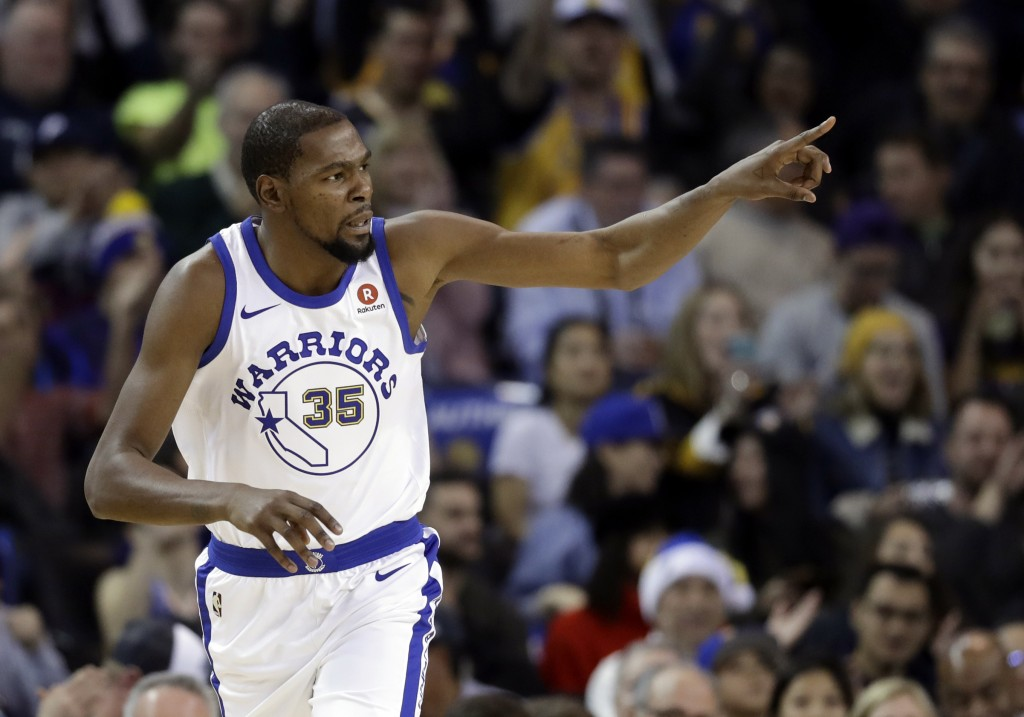Golden State Warriors forward Kevin Durant points after scoring against the Los Angeles Lakers during the first half of an NBA basketball game Friday,...