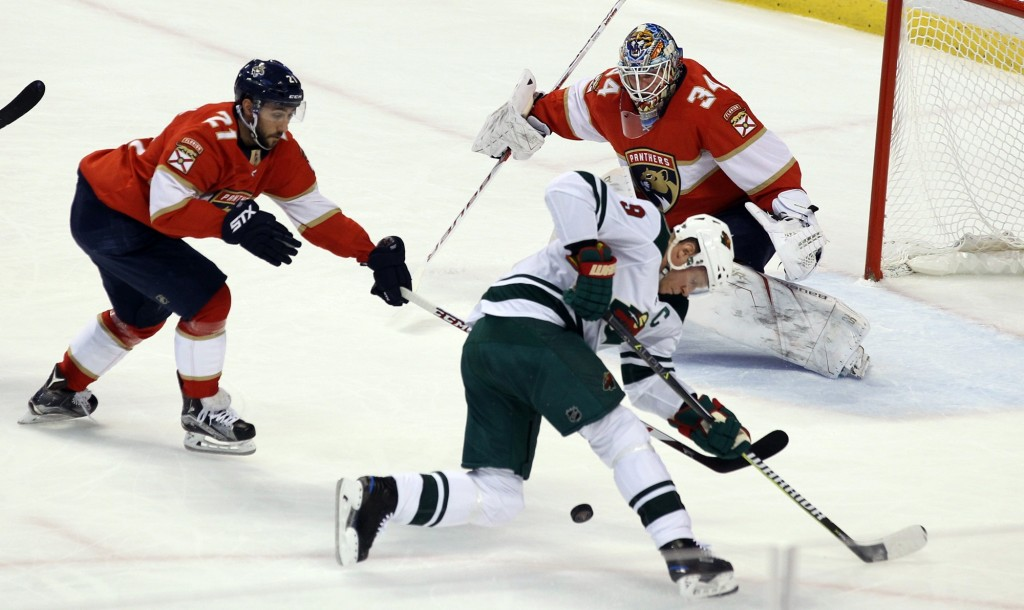 Minnesota Wild's Mikko Koivu (9), of Finland, looks for the puck as Florida Panthers goalie James Reimer (34) and Vincent Trocheck (21) defend during ...