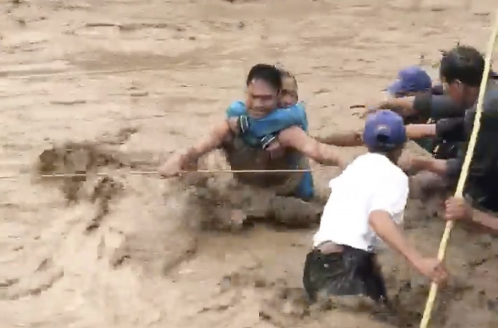 In this photo made from video by Aclimah Disumala, Friday, Dec. 22, 2017, villagers carry an elderly woman across raging flood waters in Lanao del Nor...
