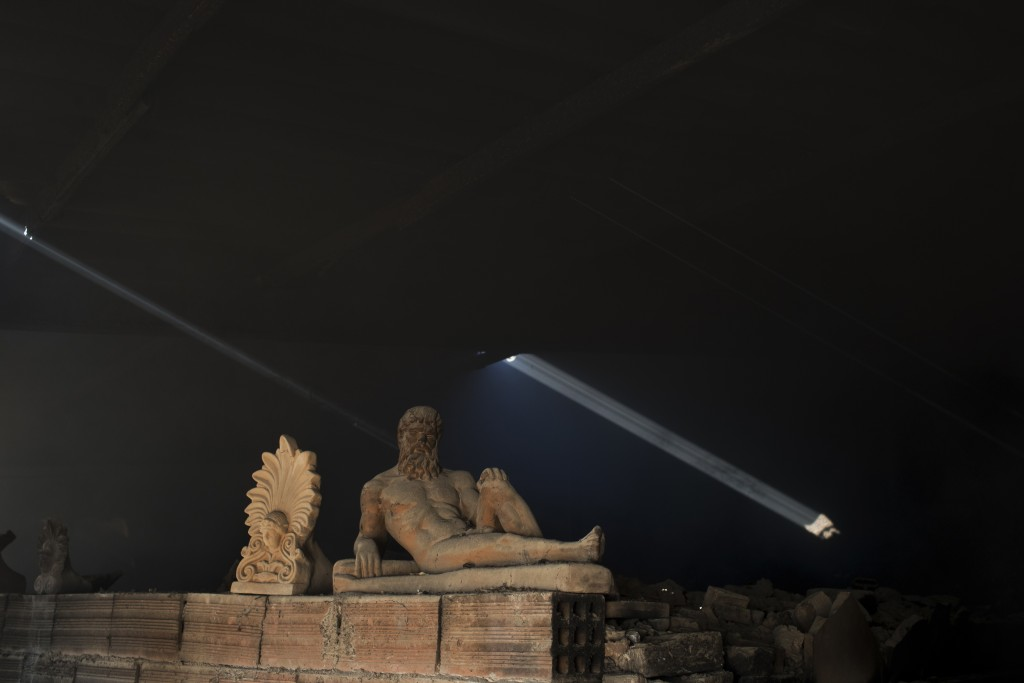In this Friday, Nov. 20, 2017 photo, a sooty, dust-covered terracotta statue of Greek mythological hero Hercules, a son of Zeus, stands on top of a bu...