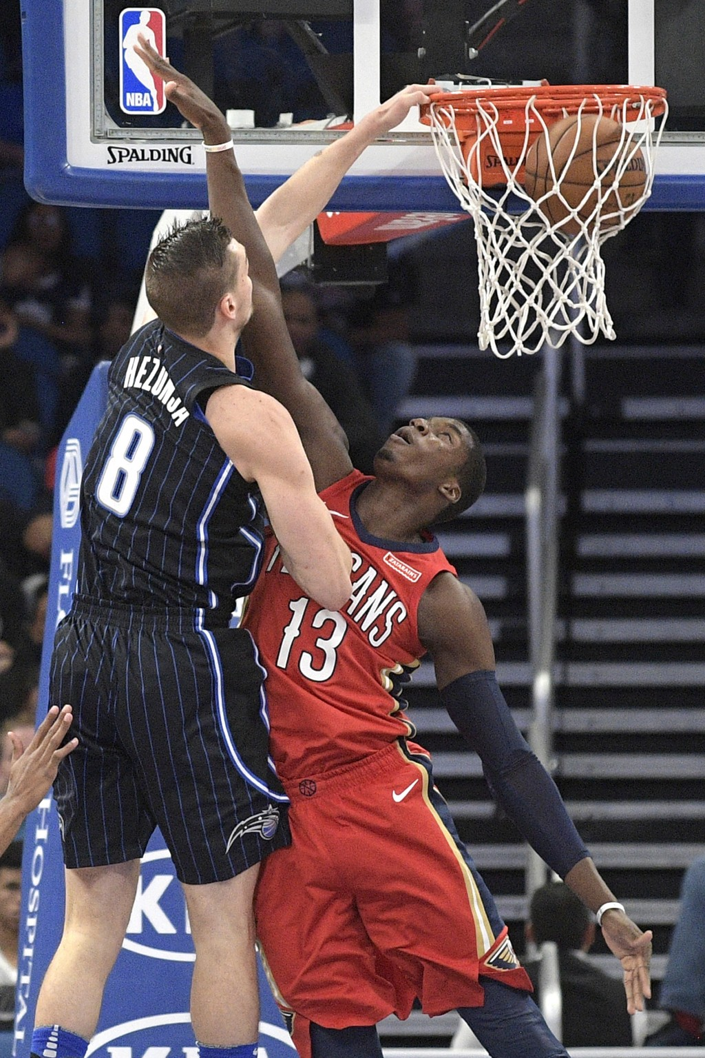 Orlando Magic guard Mario Hezonja (8) dunks over New Orleans Pelicans forward Cheick Diallo (13) during the second half of an NBA basketball game Frid...