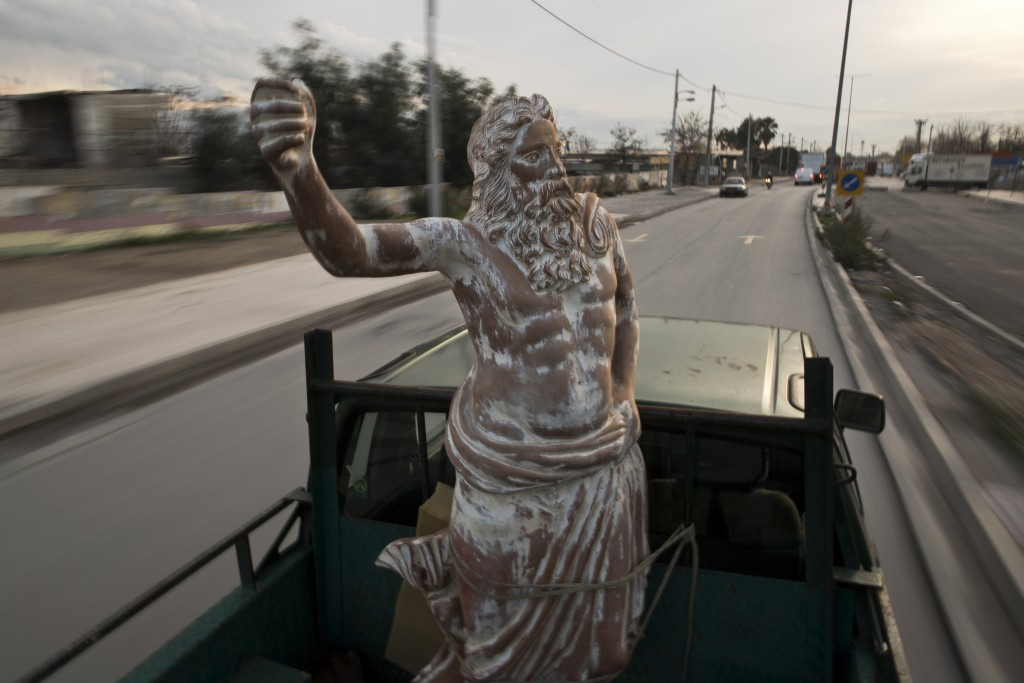 In this Tuesday, Dec 19, 2017 photo, a pickup track drives on a street of Athens carrying a terracotta statue of Zeus, chief among the ancient Greek g...