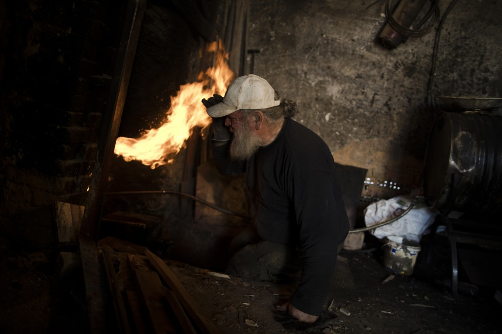 In this Friday, Nov. 20, 2017 photo, sculptor and ceramicist Haralambos Goumas looks into the fire as he tries to control the temperature of the furna...