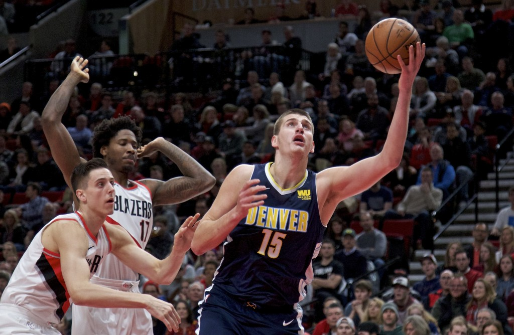 Denver Nuggets center Nikola Jokic, right, shoots past Portland Trail Blazers center Zach Collins, left, and forward Ed Davis, center, during the firs...