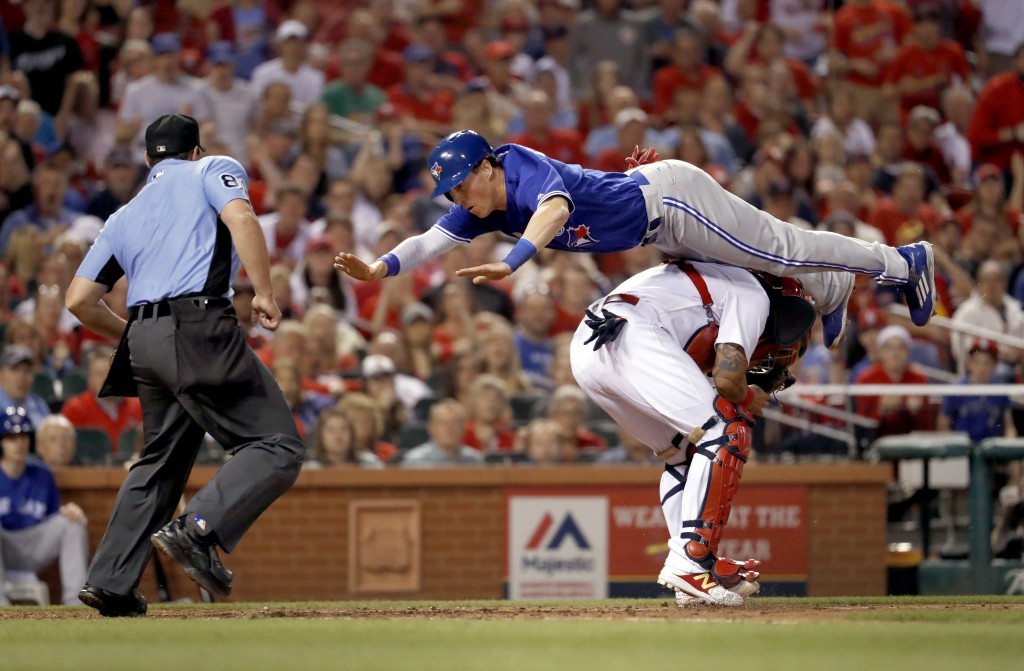 FILE - In this April 25, 2017, file photo, Toronto Blue Jays' Chris Coghlan, top, leaps over St. Louis Cardinals catcher Yadier Molina to score during...