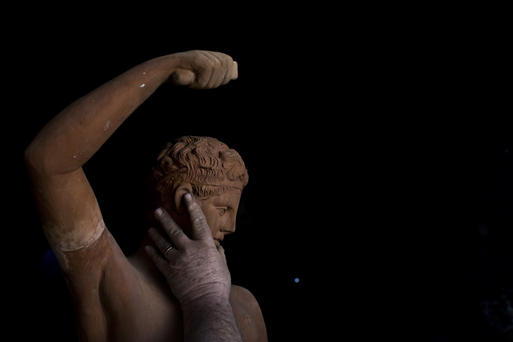 In this Tuesday, Dec. 19, 2017 photo, sculptor and ceramicist Haralambos Goumas touches a terracotta statue of Hermes, messenger of the ancient Greek ...