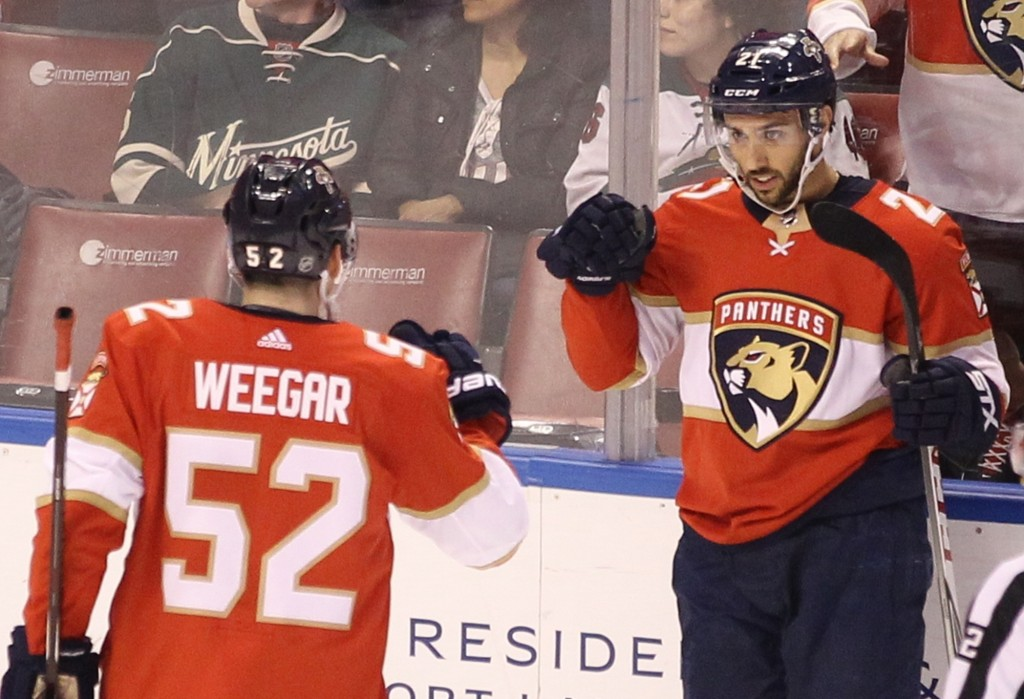 Florida Panthers' Vincent Trocheck, right, celebrates with teammate MacKenzie Weegar (52) after scoring a goal against the Minnesota Wild during the f...