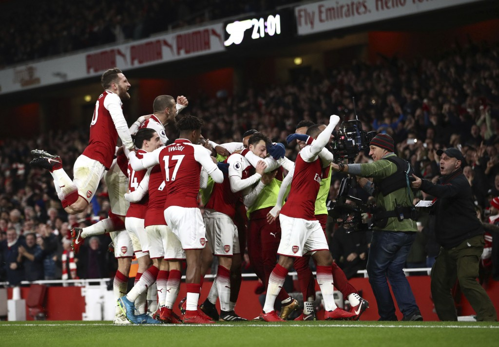 Arsenal's Mesut Ozil, centre, celebrates with teammates after scoring his side's third goal of the game during their English Premier League soccer mat...