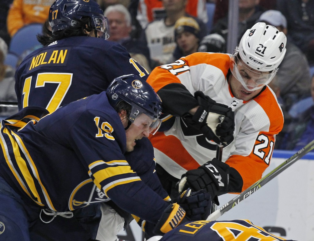 Buffalo Sabres defenseman Jake McCabe (19) checks Philadelphia Flyers forward Scott Laughton (21) during the second period of an NHL hockey game, Frid...