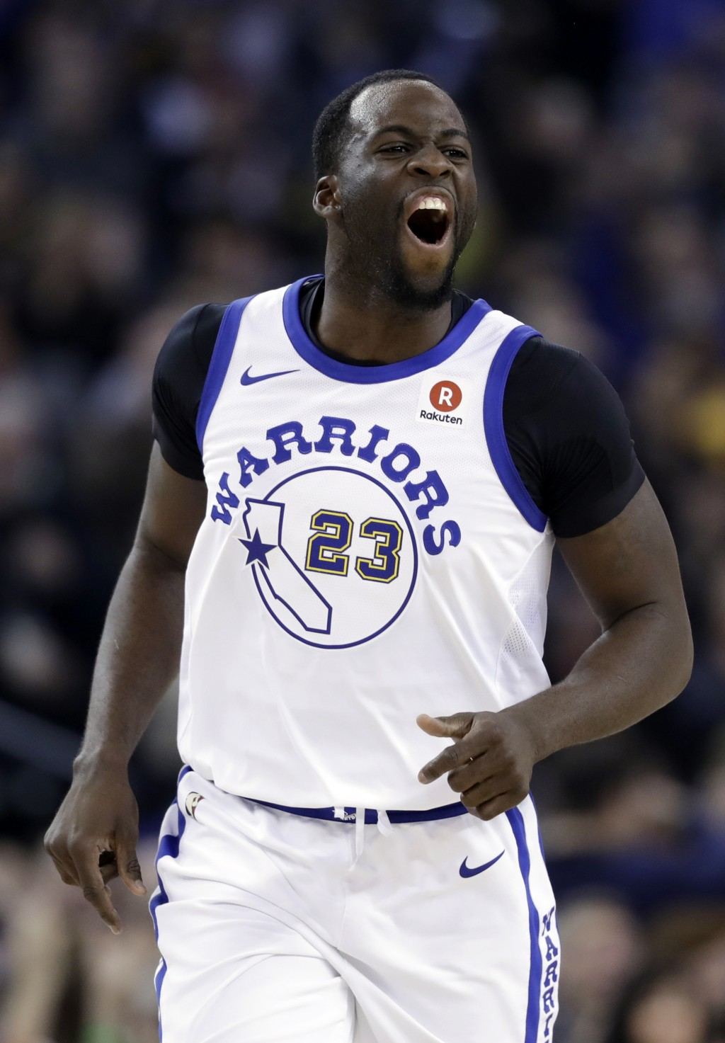 Golden State Warriors forward Draymond Green yells after scoring against the Los Angeles Lakers during the first half of an NBA basketball game Friday...