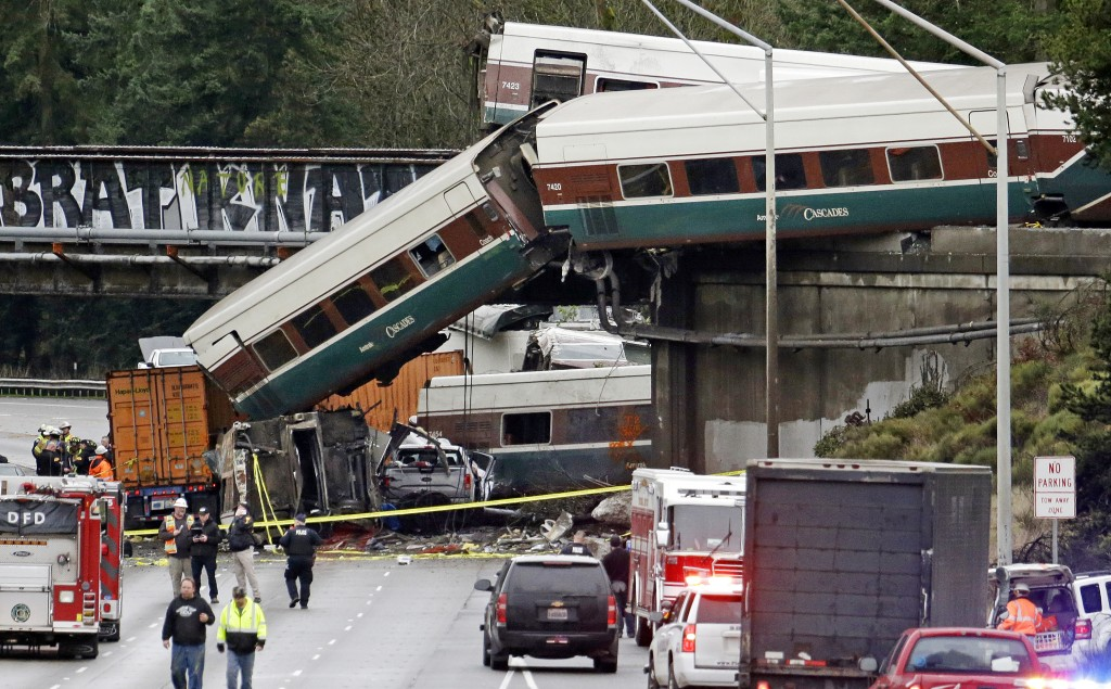 FILE - In this Dec. 18, 2017 file photo, cars from a derailed Amtrak train spill onto Interstate 5 in DuPont, Wash. On Friday, Dec. 22, 2017, The Asso...