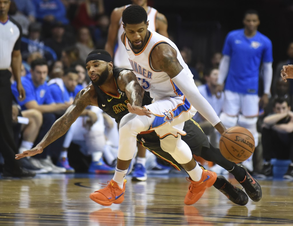 Oklahoma City Thunder's Paul George (13) tries to keep the ball away from Atlanta's Malcolm Delaney in the fourth quarter of an NBA basketball game in...