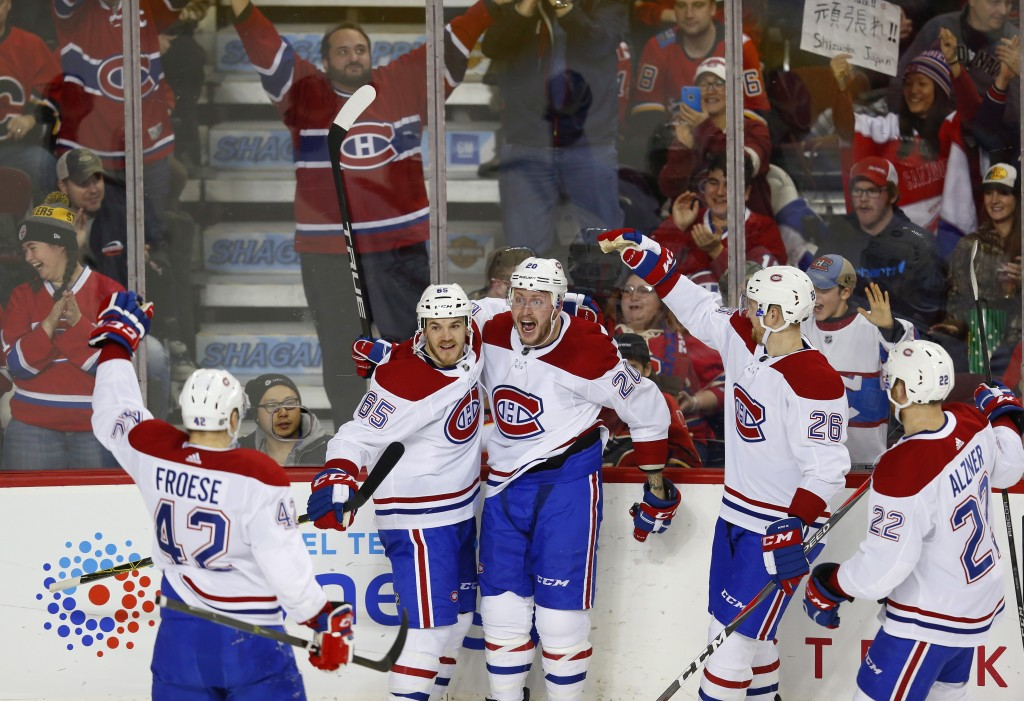 Montreal Canadiens' Nicolas Deslauriers (20) celebrates his goal against the Calgary Flames with teammates Andrew Shaw (65), Byron Froese (42), Jeff P...