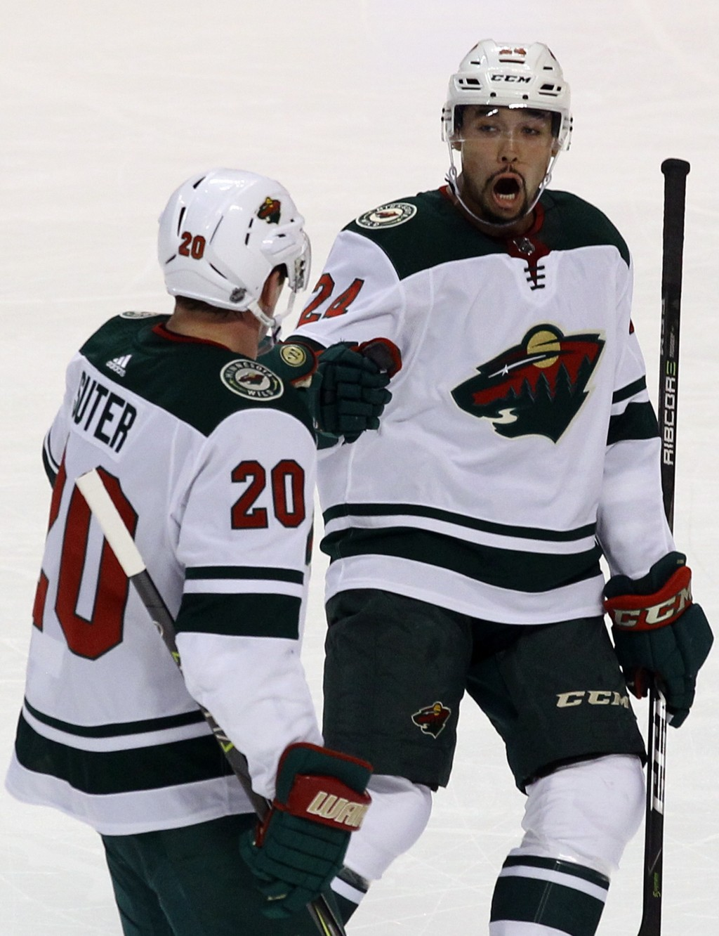 Minnesota Wild's Ryan Suter (20) celebrates with teammate Matt Dumba (24) after scoring a goal against the Florida Panthers during the first period of...