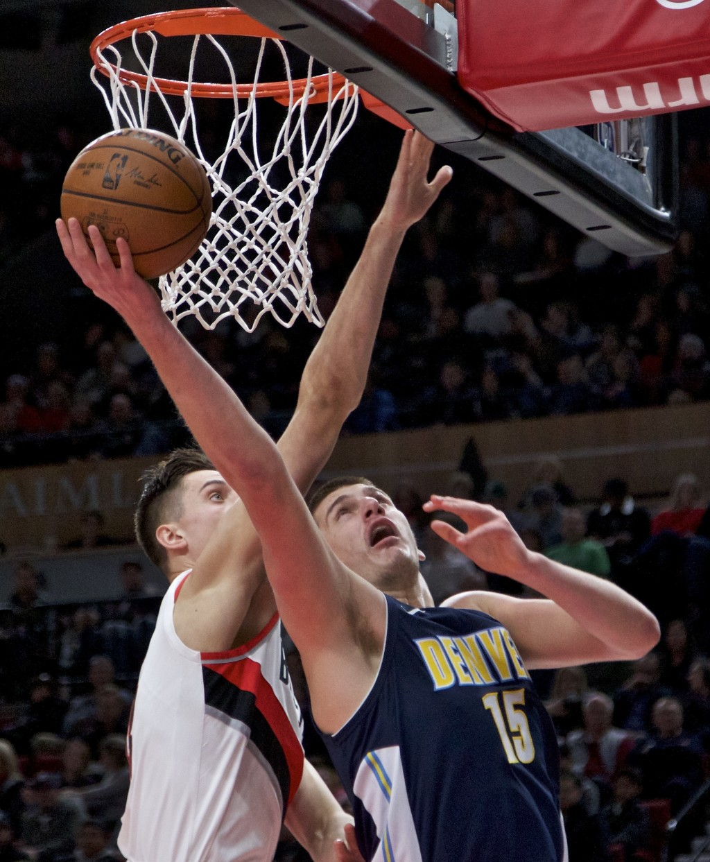 Denver Nuggets center Nikola Jokic, right, shoots over Portland Trail Blazers center Zach Collins during the first half of an NBA basketball game in P...