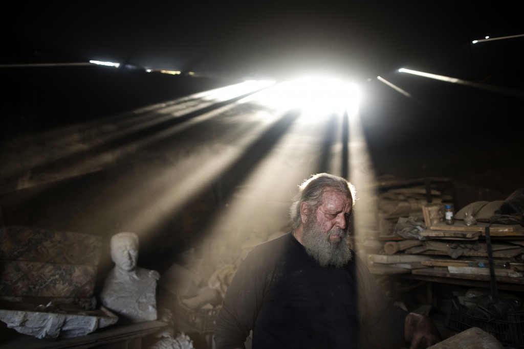 In this Friday, Nov. 20, 2017 photo, rays of sunlight shine on sculptor and ceramicist Haralambos Goumas as he works in his workshop, in the Egaleo su...