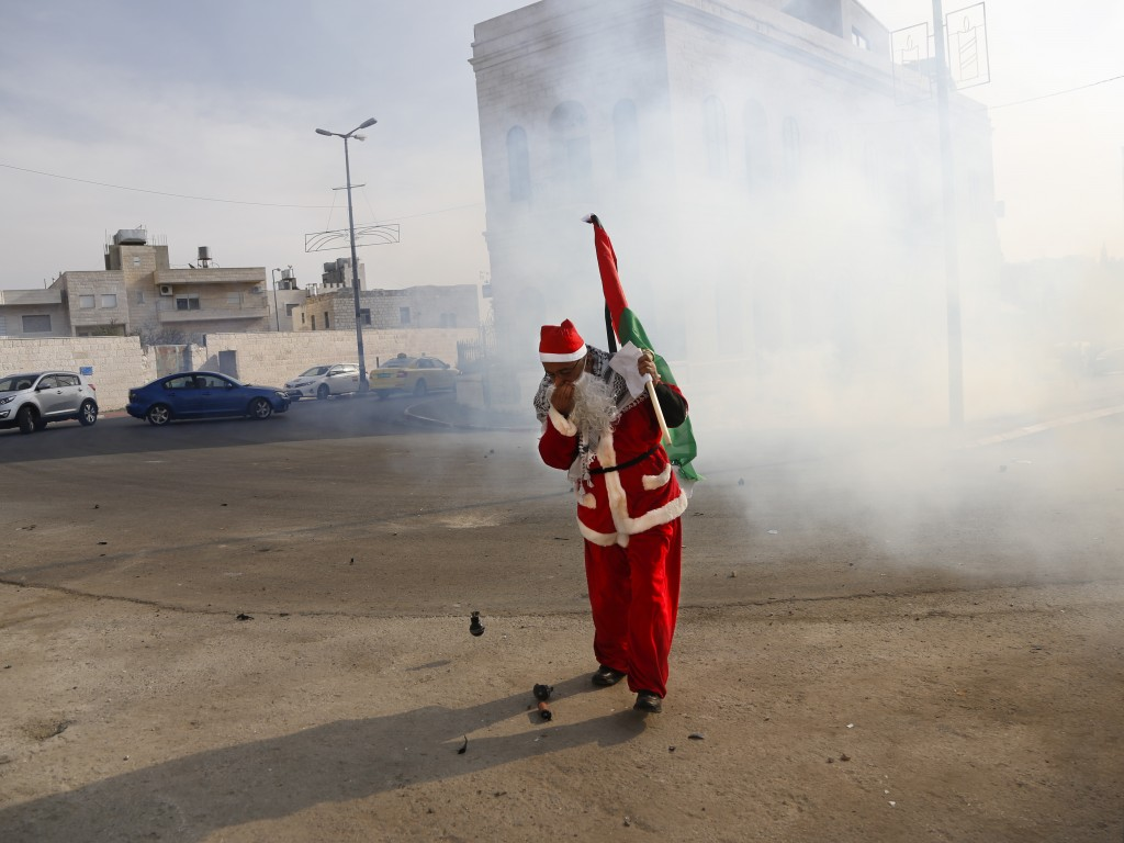 A Palestinian dressed as Santa Claus covers his nose from teargas thrown by Israeli border police during a protest in the West Bank city of Bethlehem,...