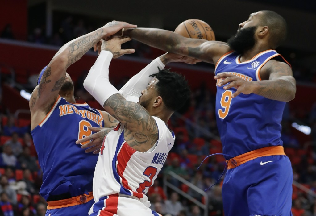 New York Knicks forward Michael Beasley (8) and center Kyle O'Quinn (9) block a shot by Detroit Pistons forward Eric Moreland (24) during the first ha...
