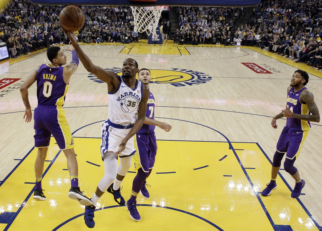 Golden State Warriors forward Kevin Durant (35) drives past Los Angeles Lakers' Kyle Kuzma (0), Larry Nance Jr. (7) and Brandon Ingram, right, during ...