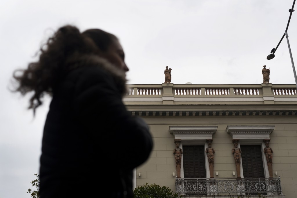 In this Thursday, Dec. 21, 2017 photo, a woman walks past a neoclassical building decorated with terracotta statues of the muses, on the roof, and Atl...