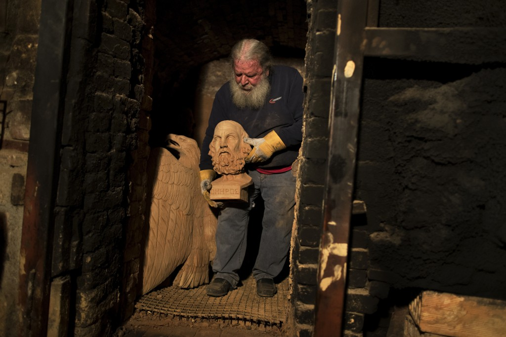 In this Thursday, Dec. 21, 2017 sculptor and ceramicist Haralambos Goumas carries out of a furnace the bust of Homer, whom Greek tradition named as th...