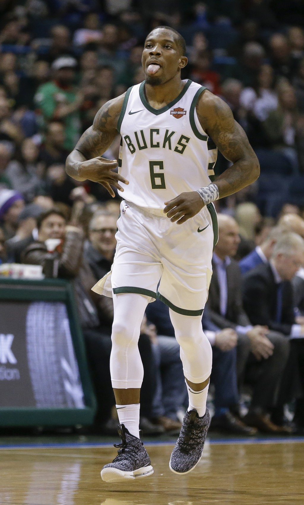 Milwaukee Bucks' Eric Bledsoe signals after hitting a three-point basket against the Charlotte Hornets during the first half of an NBA basketball game...