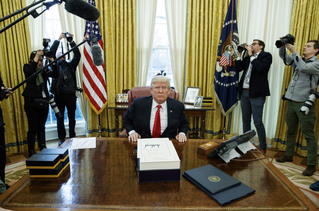 President Donald Trump speaks to reporters after signing the tax bill and continuing resolution to fund the government, in the Oval Office of the Whit...