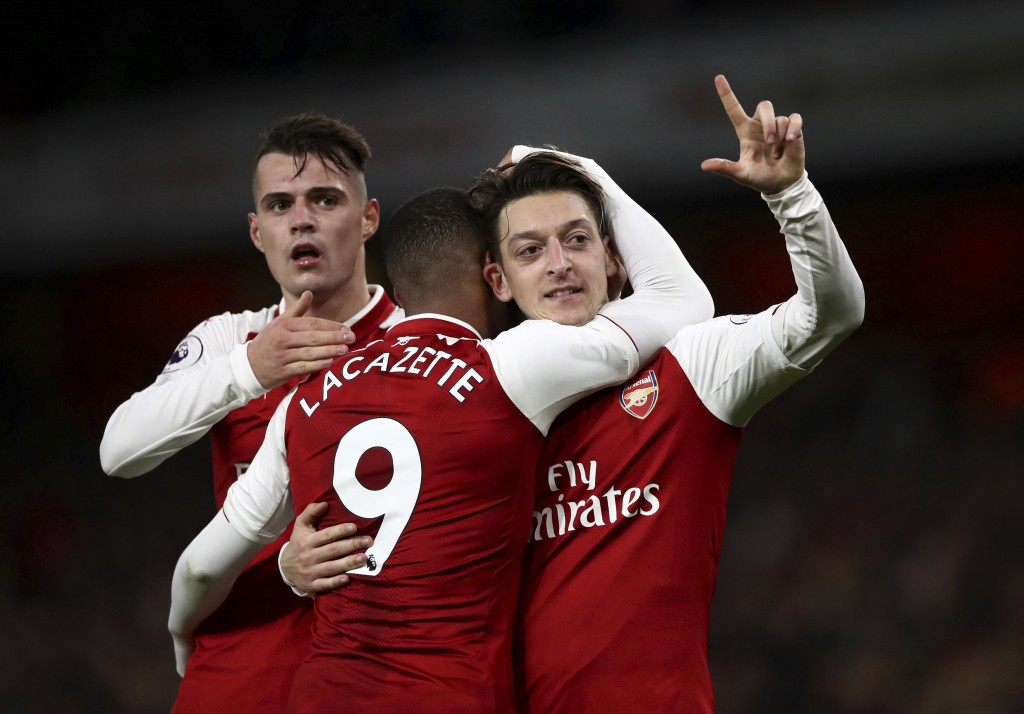 Arsenal's Mesut Ozil, right, celebrates scoring his side's third goal of the game during their English Premier League soccer match between Arsenal and...