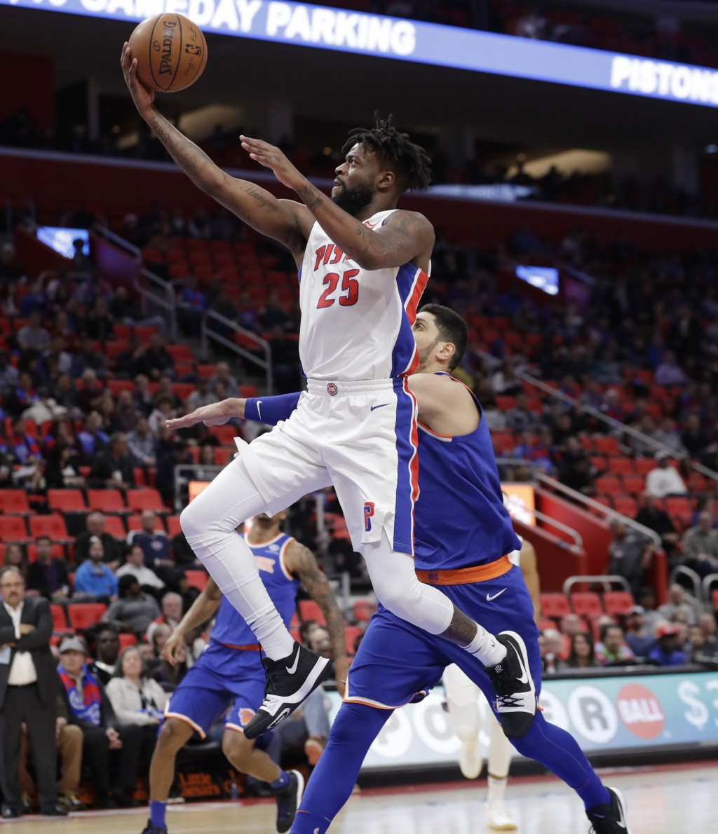 Detroit Pistons forward Reggie Bullock (25) makes a layup while defended by New York Knicks center Enes Kanter (00) during the first half of an NBA ba...