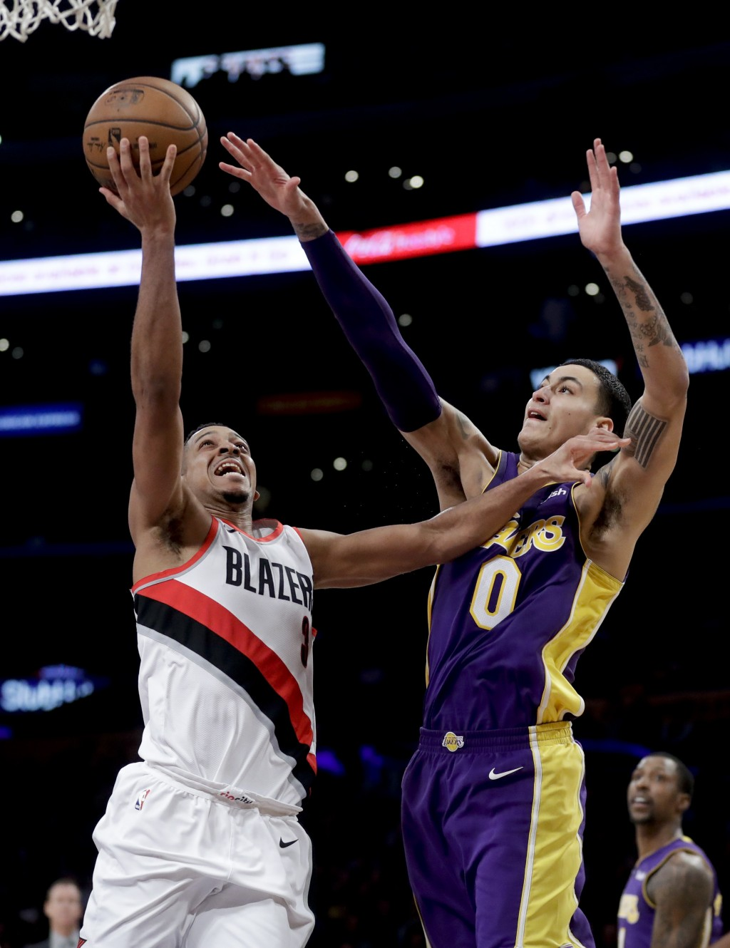 Portland Trail Blazers guard CJ McCollum, left, shoots next to Los Angeles Lakers forward Kyle Kuzma during the second half of an NBA basketball game ...