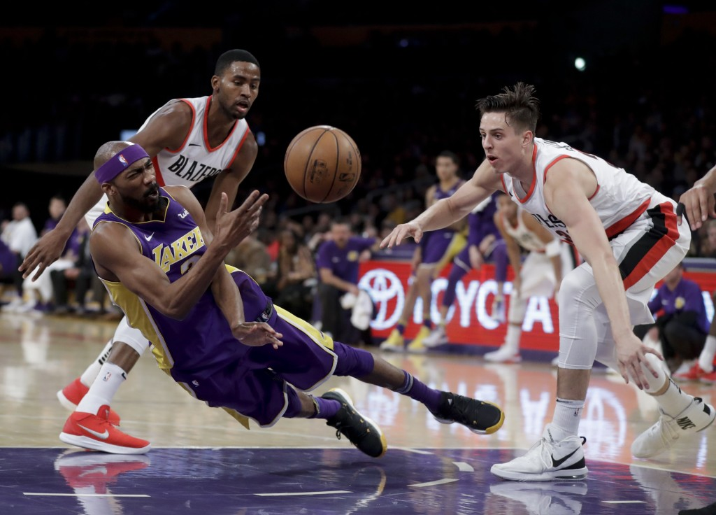 Los Angeles Lakers forward Corey Brewer, middle, passes between Portland Trail Blazers forward Maurice Harkless, left, and guard CJ Wilcox during the ...