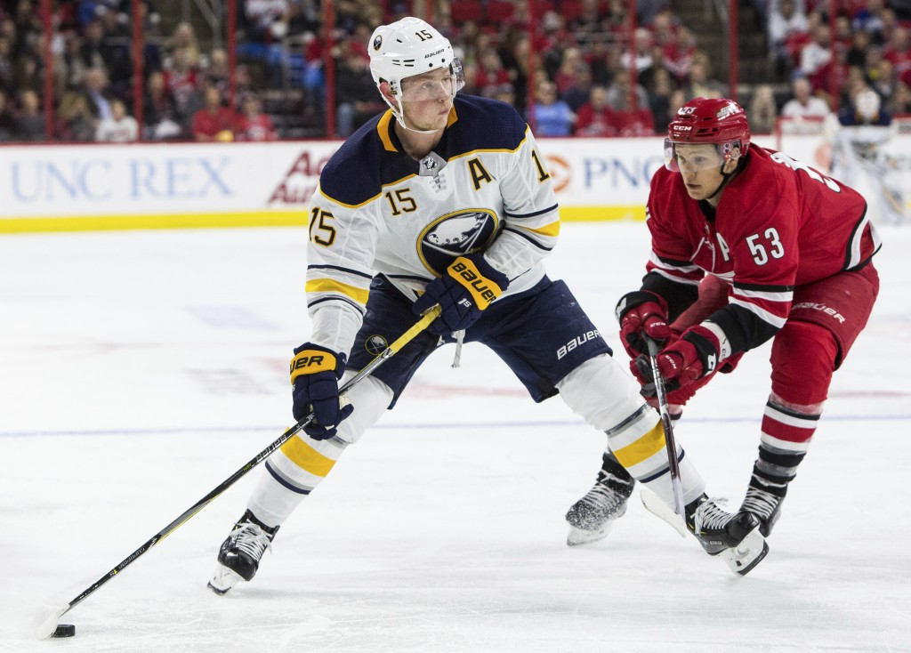 Buffalo Sabres' Jack Eichel (15) handles the puck ahead of Carolina Hurricanes' Jeff Skinner (53) during the first period of an NHL hockey game in Ral...