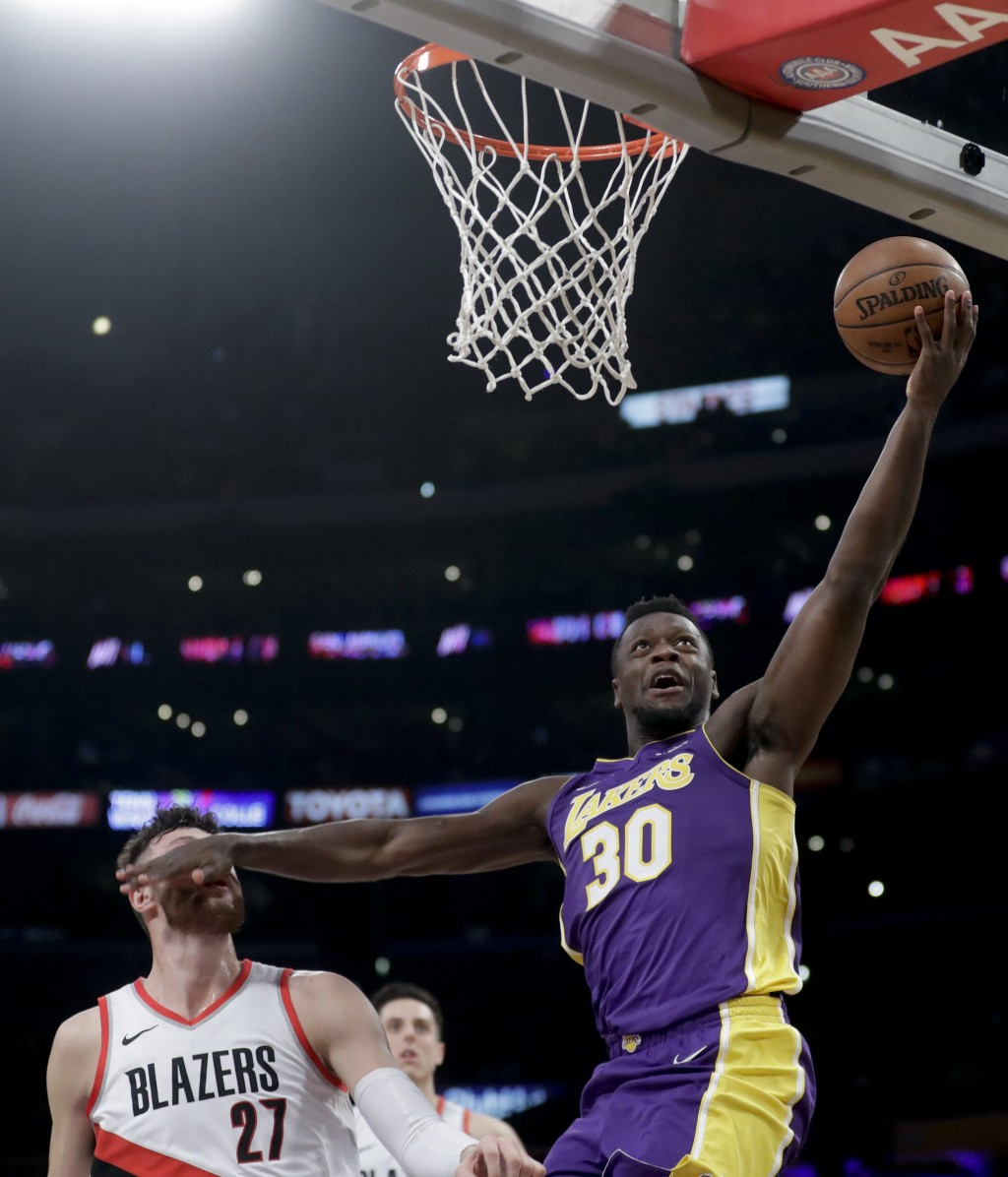 Los Angeles Lakers forward Julius Randle, right, fouls Portland Trail Blazers center Jusuf Nurkic during the first half of an NBA basketball game in L...