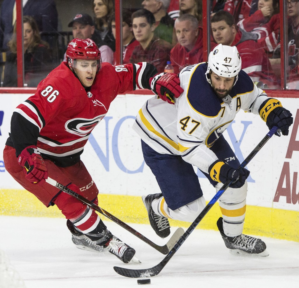 Buffalo Sabres' Zach Bogosian (47) and Carolina Hurricanes' Tuevo Teravainen (86), of Finland, fight for the puck during the second period of an NHL h...
