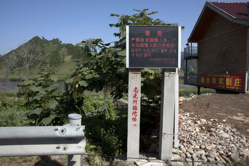 In this Aug. 30, 2017 photo, a sign in Chinese and Korean characters warns against harboring or feeding North Koreans who cross into a village near Li...
