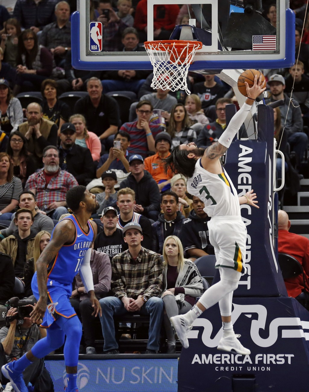 Utah Jazz guard Ricky Rubio (3) lays the ball up as Oklahoma City Thunder forward Paul George, left, looks on in the first half during an NBA basketba...