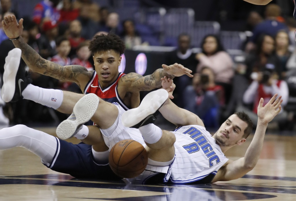 Washington Wizards forward Kelly Oubre Jr., left, competes for a loose ball with Orlando Magic guard Mario Hezonja, from Croatia, during the first hal...