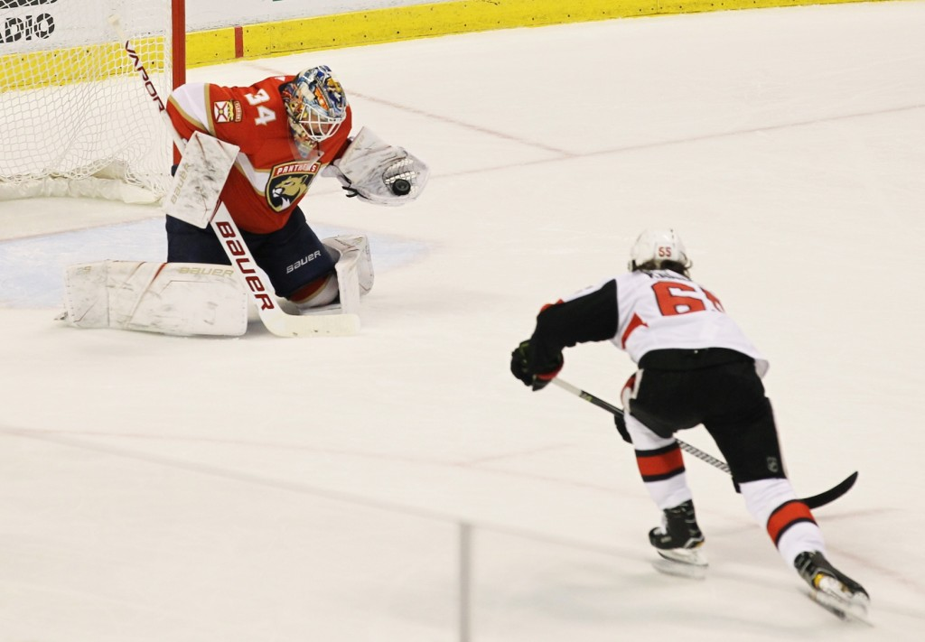 Florida Panthers goalie James Reimer (34) makes a save against Ottawa Senators' Erik Karlsson, right, of Sweden, during the second period of an NHL ho...