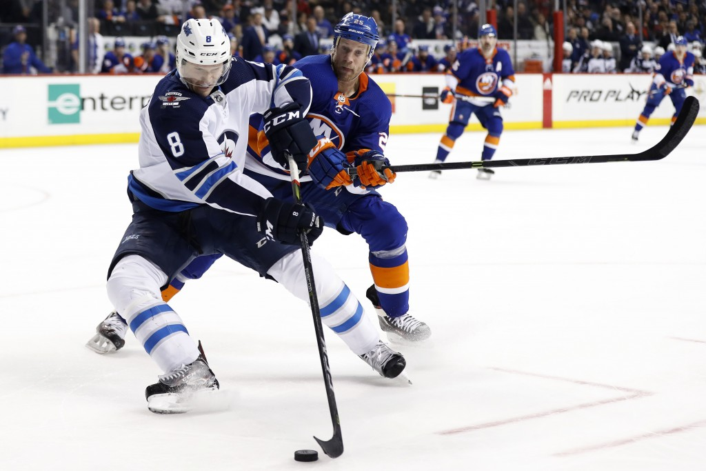 Winnipeg Jets defenseman Jacob Trouba (8) controls the puck in front of New York Islanders left wing Jason Chimera in the second period of an NHL hock...