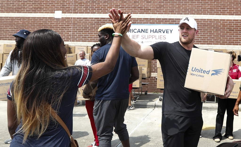FILE - In this Sunday, Sept. 3, 2017, file photo, Anna Ucheomumu, left, high fives Houston Texans defensive end J.J. Watt after loading a car with rel...
