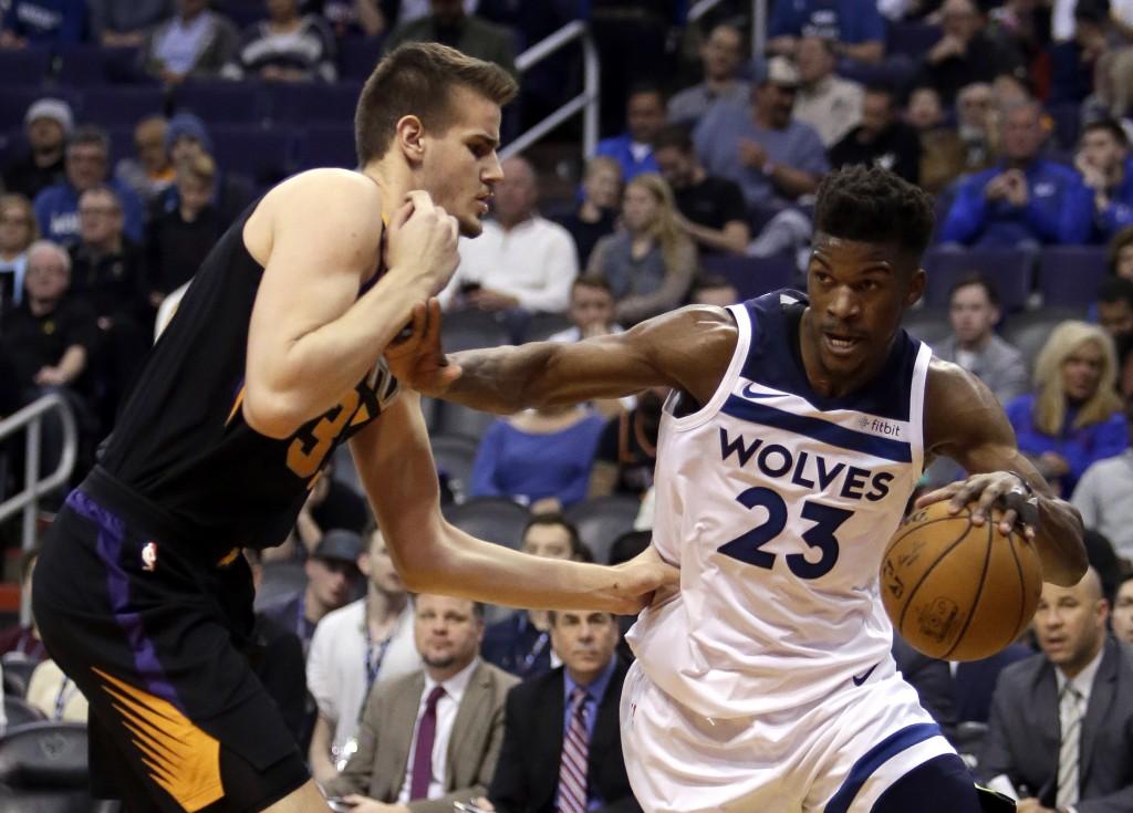 Minnesota Timberwolves guard Jimmy Butler (23) drives against Phoenix Suns forward Dragan Bender in the second quarter during an NBA basketball game, ...