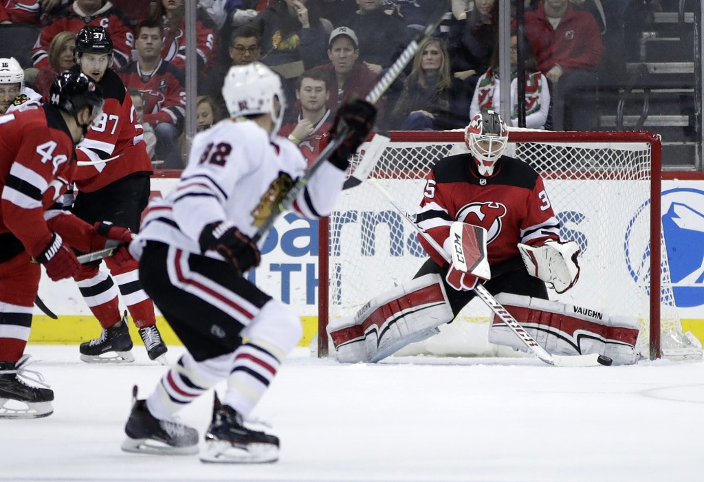 New Jersey Devils goalie Cory Schneider right, deflects a shot by the Chicago Blackhawks during the second period of an NHL hockey game, Saturday, Dec...