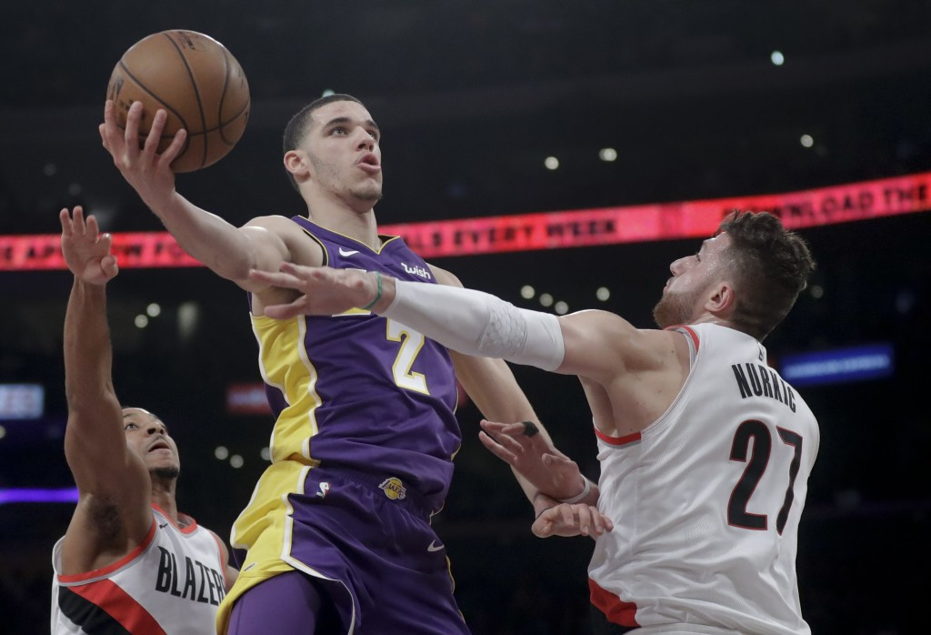 Los Angeles Lakers guard Lonzo Ball shoots between Portland Trail Blazers guard CJ McCollum, left, and center Jusuf Nurkic during the first half of an...
