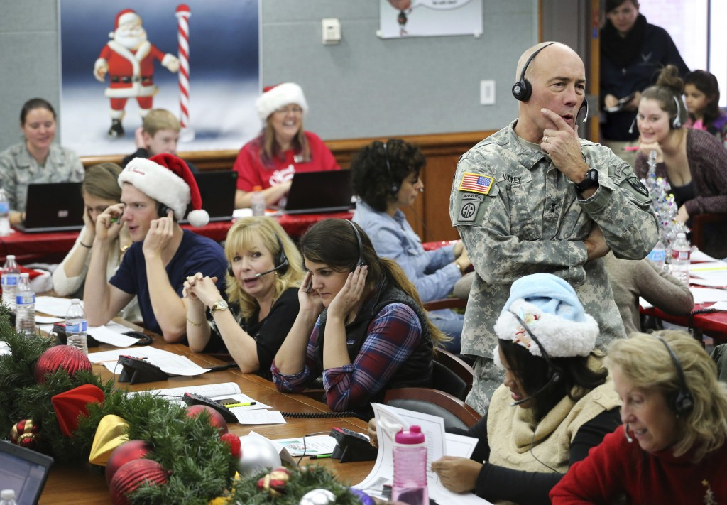 FILE - In this Dec. 24, 2014, file photo, NORAD and USNORTHCOM Chief of Staff Maj. Gen. Charles D. Luckey joins other volunteers taking phone calls fr...