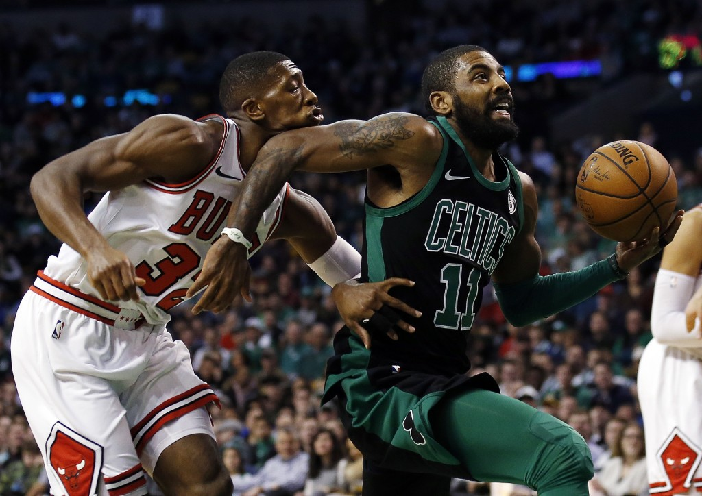 Boston Celtics' Kyrie Irving elbows Chicago Bulls' Kris Dunn on the face as he goes past Dunn to the basket during the first quarter of an NBA basketb...