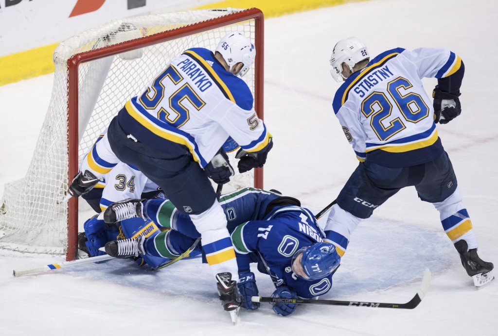 Vancouver Canucks' Nikolay Goldobin (77), of Russia, is checked to the ice by St. Louis Blues' Colton Parayko (55) in front of goalie Jake Allen and P...