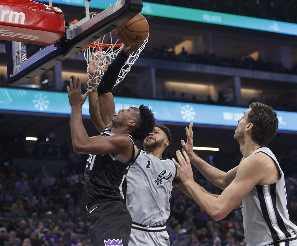 Sacramento Kings guard Buddy Hield (24) drives to the basket against San Antonio Spurs' Kyle Anderson (1) and Pau Gasol during the first half of an NB...