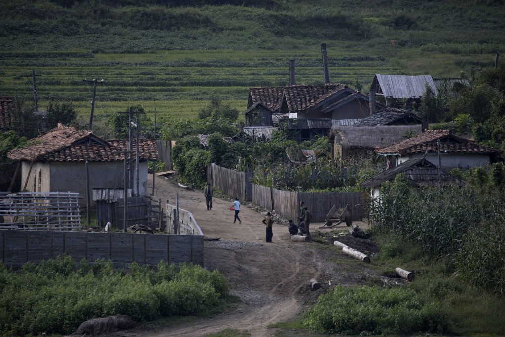 In this Aug. 30, 2017 photo, North Koreans walk through a village on the banks of the Yalu river across from the Chinese border town of Linjiang north...
