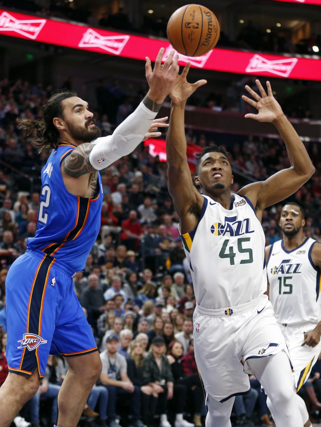 Utah Jazz guard Donovan Mitchell (45) and Oklahoma City Thunder center Steven Adams, left, battle for a rebound in the first half during an NBA basket...