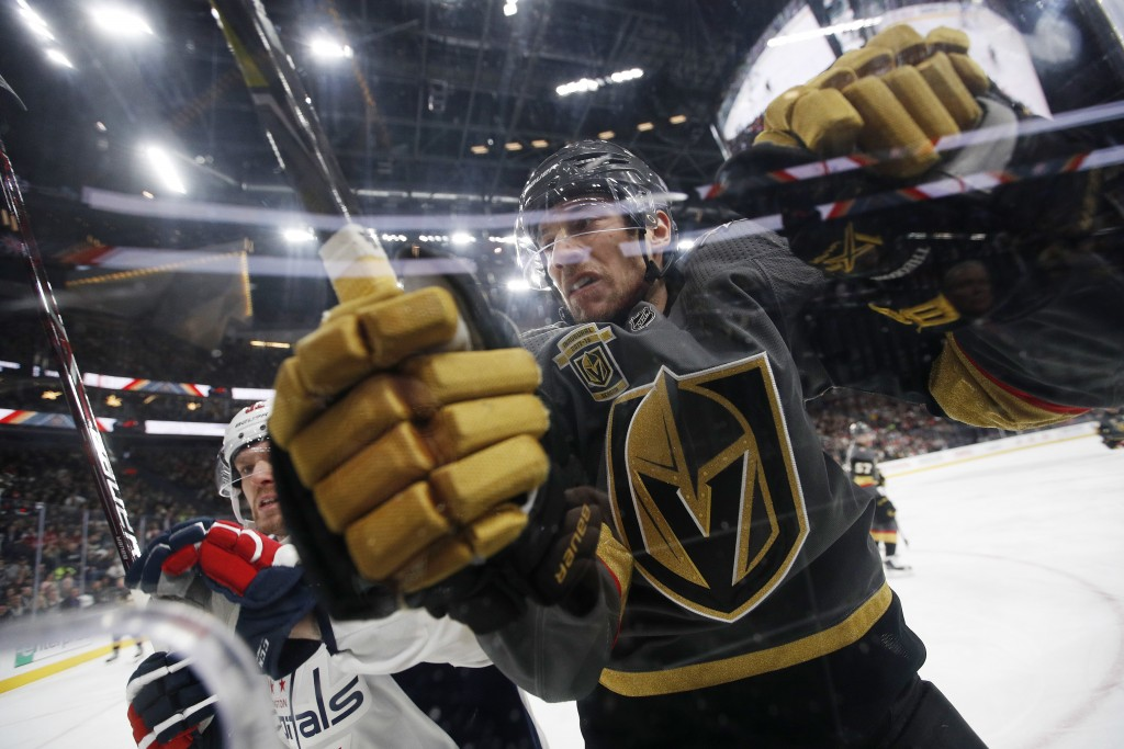 Washington Capitals center Evgeny Kuznetsov, left, checks Vegas Golden Knights defenseman Shea Theodore into the boards during the first period of an ...